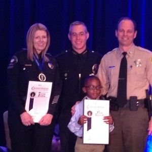 Public Safety Dispatcher Teresa Griffitts and six year old, Noah Anumudu being awarded.
