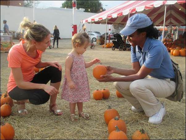 A Helpful Honda Person giving a child a pumpkin