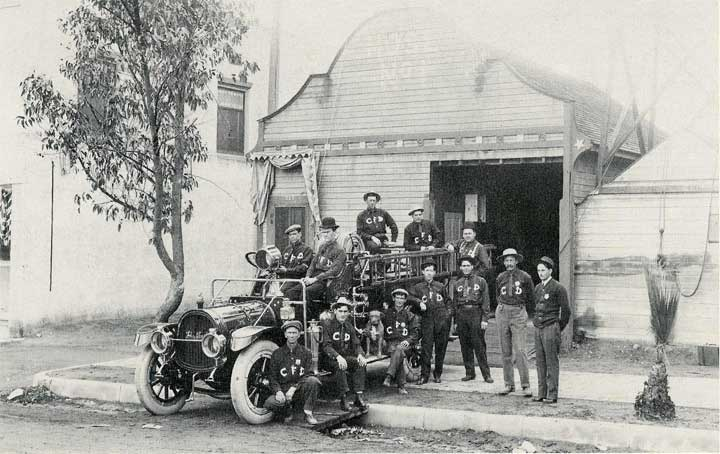 Corona's first fire station with its firefighters posing in front of their engine.